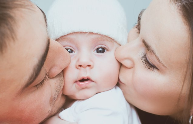 parents kissing the baby